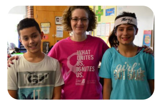students and teacher showing off their positive t-shirts